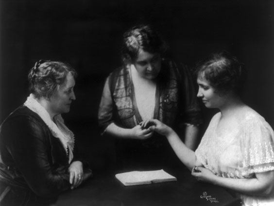 Helen Keller seated at right with mother, Kate Adams Keller, and Annie Sullivan (standing), 1914 Library of Congress